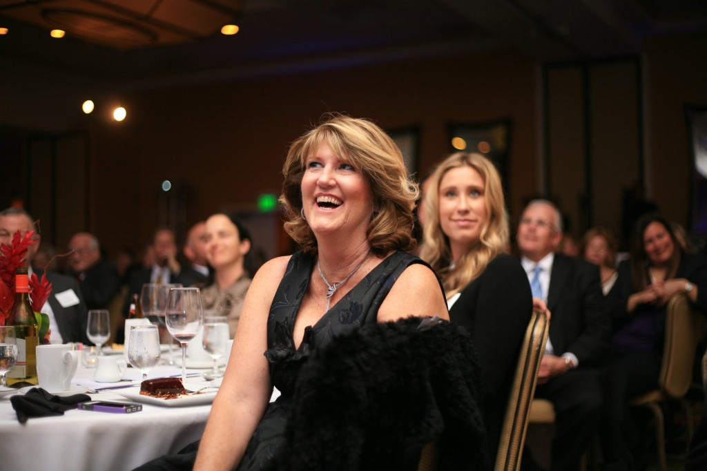 """Mayor Rush Hill's wife, Linda, laughs at a joke Hill makes during his """"State of the City"""" speech."""