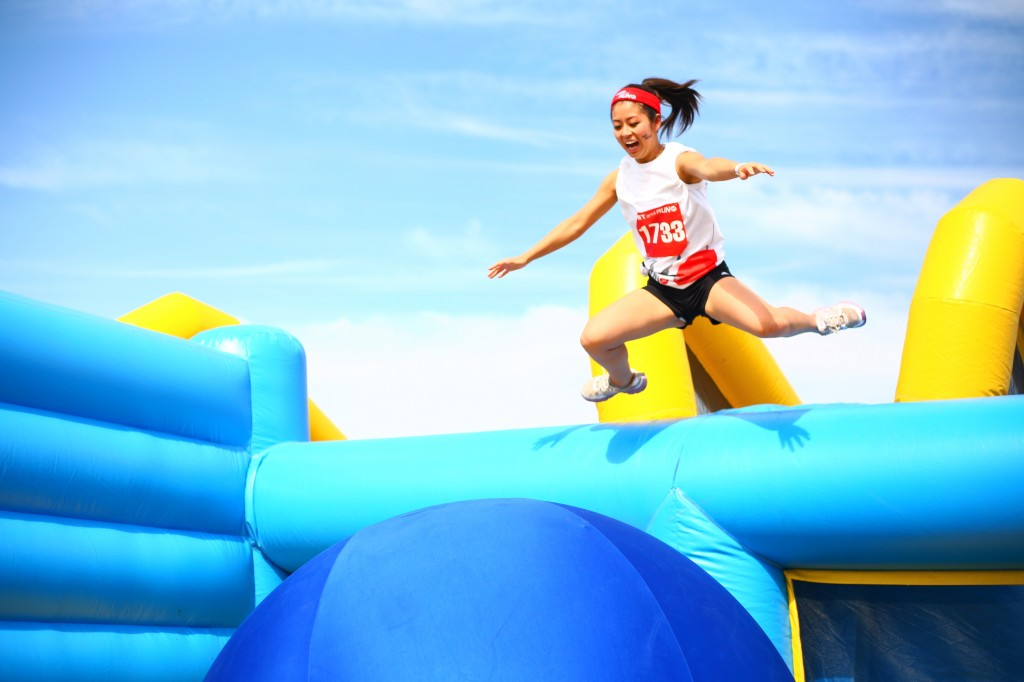 A Hit and Run participant jumps into the second obstacle along the course, the Bouncy Bridge.