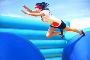 A woman leaps toward the second ball of the Bouncy Bridge obstacle.