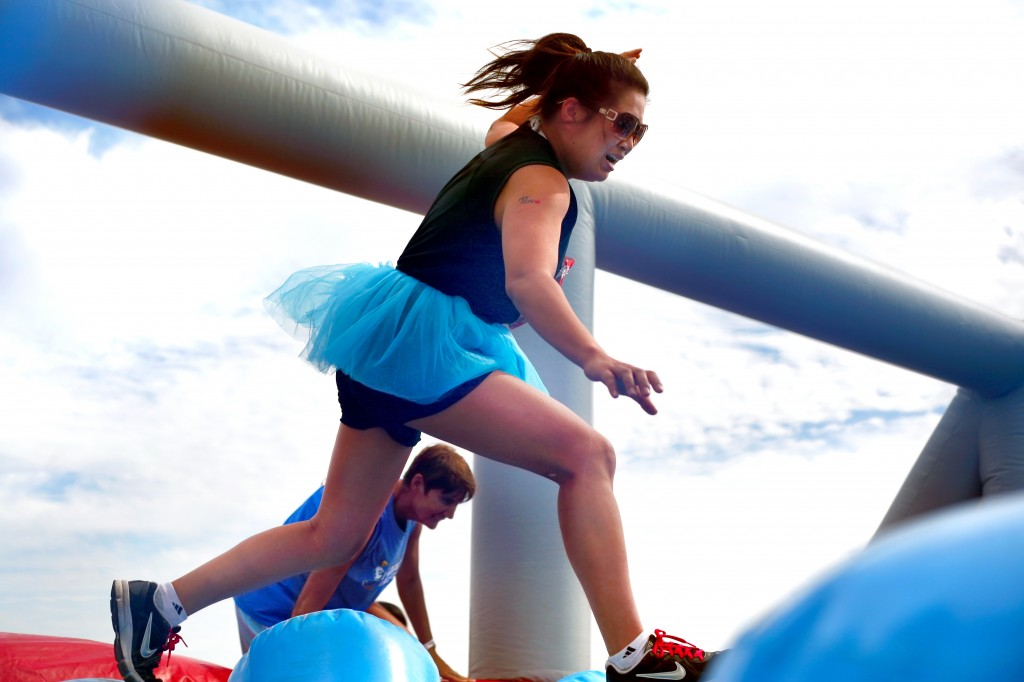 A Hit and Run participant tries to run over the inflatable posts in the Wobble Walk obstacle.