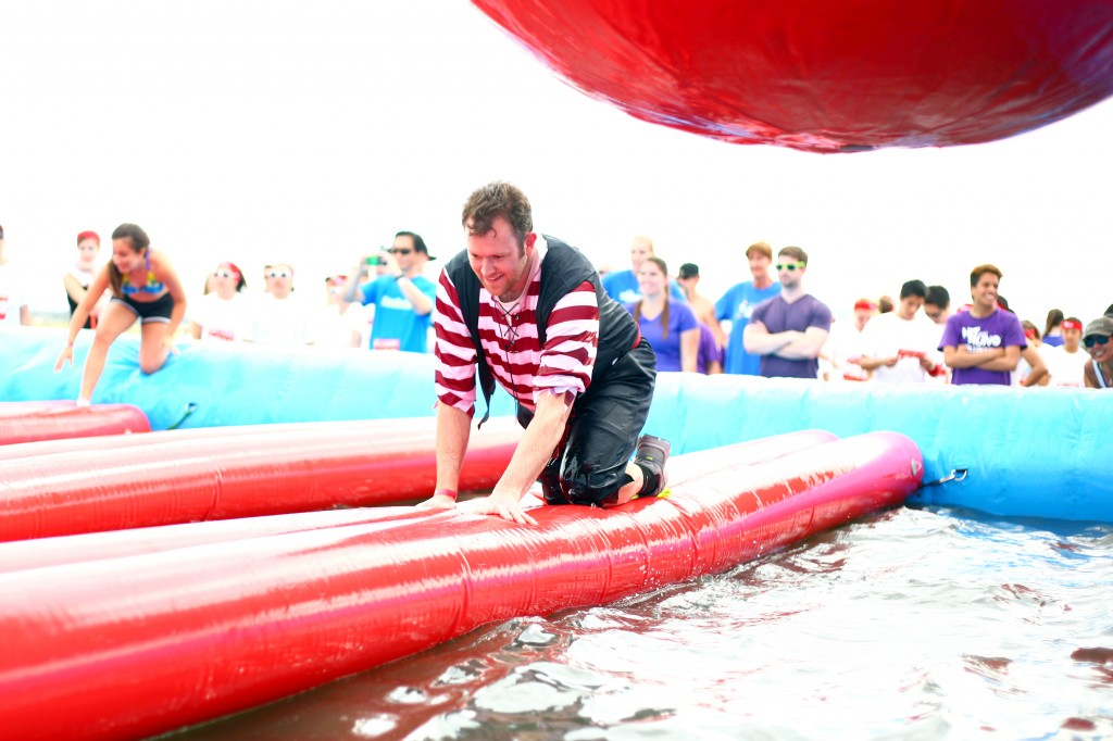 Ted Dixon crawls over a floating plank while avoid the oversized red rubber balls swinging above him.