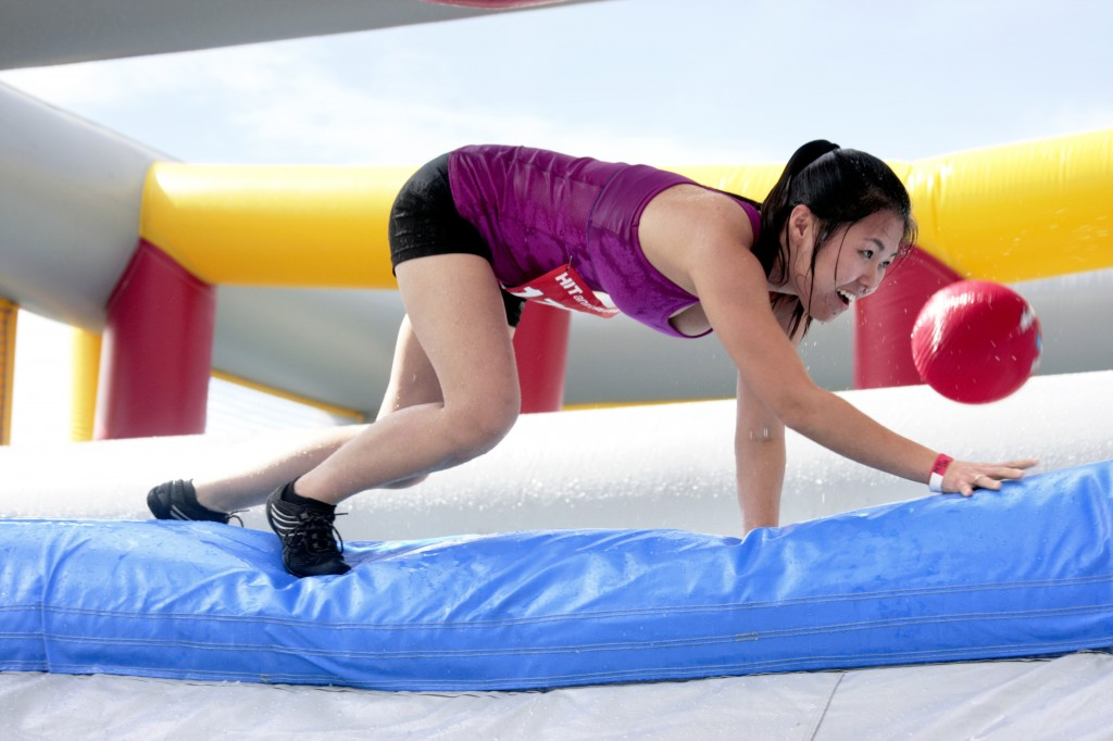 A participant crawls through an obstacle.