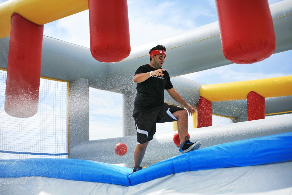 A racer runs across an inflatable ledge while dodging balls, getting hosed down and avoiding the hanging columns in the Slippery Slopes obstacle.