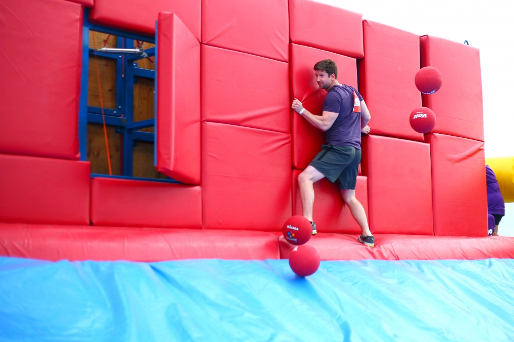 Carefully making his way across the Whacking Wall, a man holds on to one of the sections that pop out as he gets bombarded with red bouncy balls.