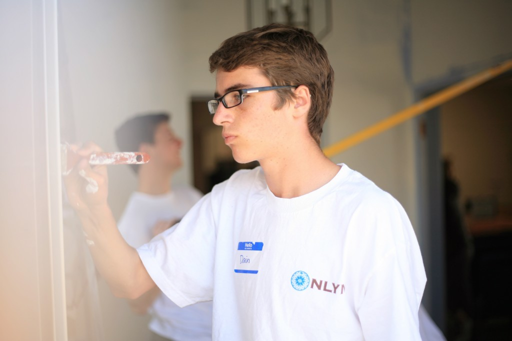 Dain Woods, 15, a sophomore at Corona del Mar High School, paints the foyer at the church as part of the group's renovation project.