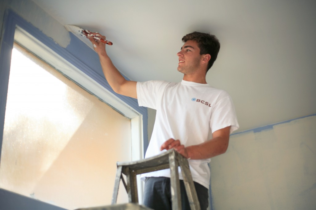 Hunter Wetton, 17, a junior at Corona del Mar High School, paints the ceiling of the foyer to the church.