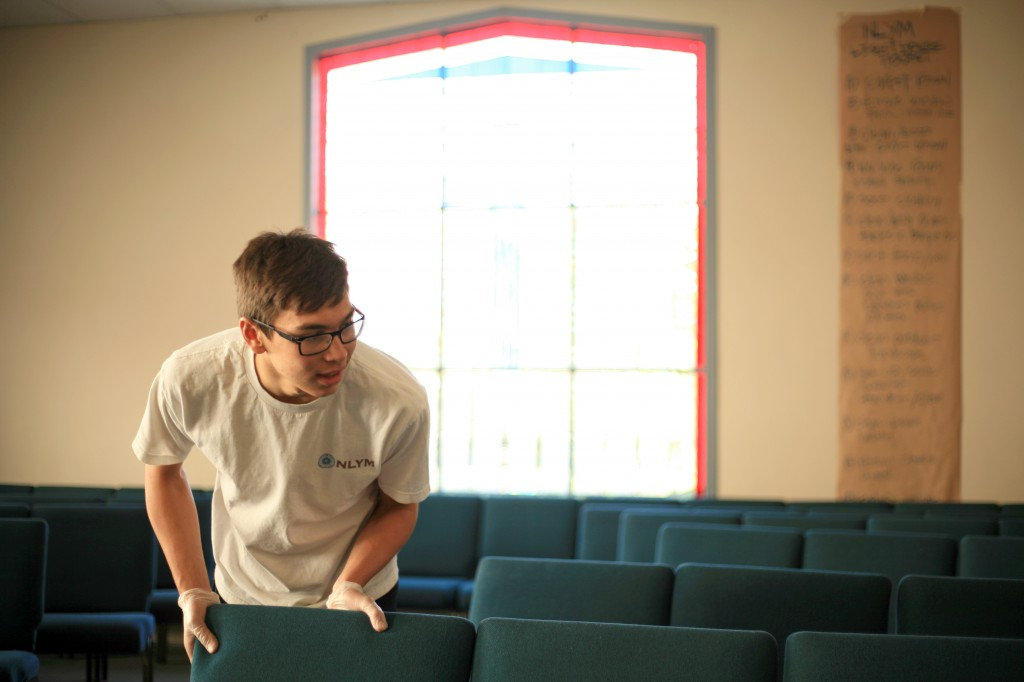 Jake Whelan, 15, a sophomore at Newport Harbor High School, arranges chairs in the congregational hall after the young men removed the carpet and cleaned the room. New carpet will be installed by professionals soon.