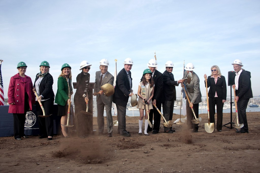 Officials break ground at the Marina Park site on Tuesday. From left to right: Girl Scouts of Orange County Board Secretary Christine Shingleton, GSOC CEO Nancy Nygren, GSOC Board Chair Julie Miller-Phipps, city council members Nancy Gardner, Tony Petros and Keith Curry, girl scout Olivia Bobrownicki, Mayor Rush Hill, Mayor Pro Tem Ed Selich, council members Mike Henn and Leslie Daigle, and city manager Dave Kiff.  — Photo by Sara Hall