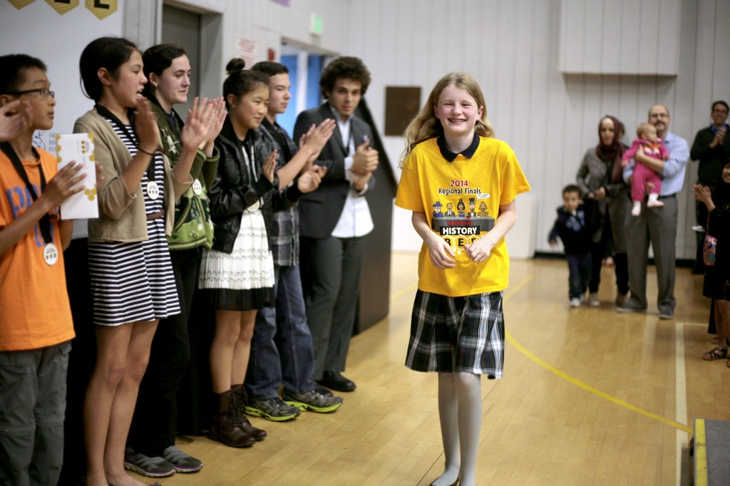 Harbor Day School fifth grader, Jean Wanlass, 11, walks up to the stage as Elementary Division Champion at the Los Angeles regional finals of the National History Bee, held Monday at the Corona del Mar campus. — All photos by Sara Hall