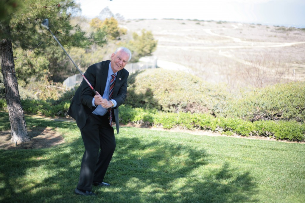 Mayor Rush Hill poses for a photo at the Newport Coast Community Center overlooking the old Coyote Canyon Landfill site in the background, where Hill proposes to build a new, affordable public golf course.  — Photo by Sara Hall