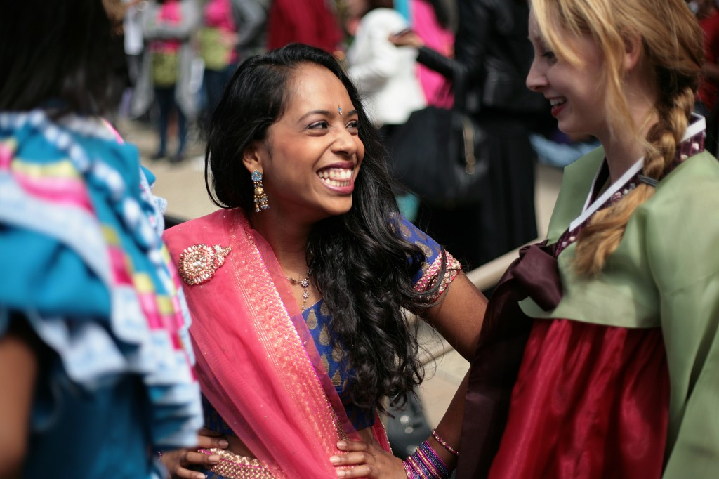 "Wearing a gagra choli, junior Rachana ""Cha Cha"" Pillai, 16, (center) laughs with classmate Becky Lynskey, 17, a senior wearing a traditional Korean hanbok, during the International Fashion Show."