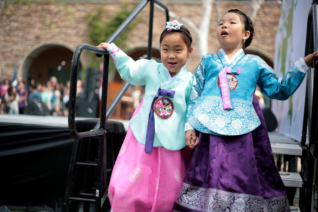 Wearing traditional Korean hanbok outfits, Lolla Rhee, 7, and Lauren Choi, 9, excitedly exit off the stage after participating in the International Fashion Show.