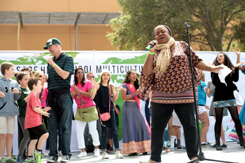 "Sage Hill's Associate Director of College Counseling, Nicole Thompson, performs the ""Happy"" song by Pharrell Williams at the Fair. Members of the audience, including Head of School Gordon McNeill and his kids (left, green shirt and cap), joined her on stage and started dancing."
