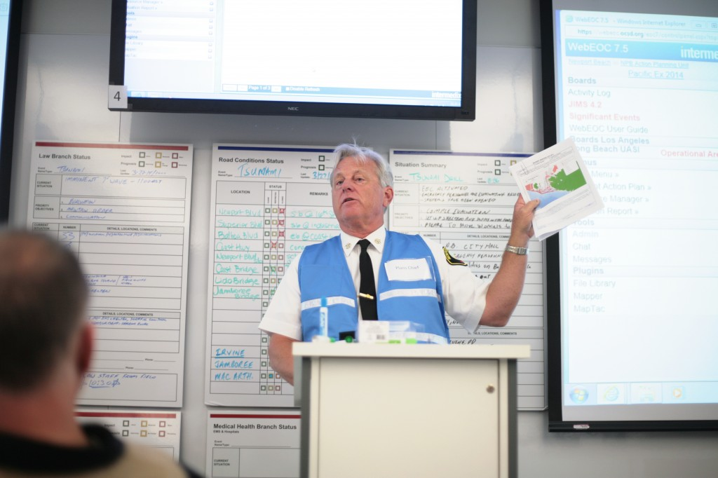 Newport Beach Fire Department Assistant Chief Kevin Kitch briefs city staff members about the Incident Action Plan during Thursday's tsunami drill at the Emergency Operations Center at the Civic Center. Behind him are law and road conditions status boards and a situation summary board that were regularly updated by staff members during the exercise.