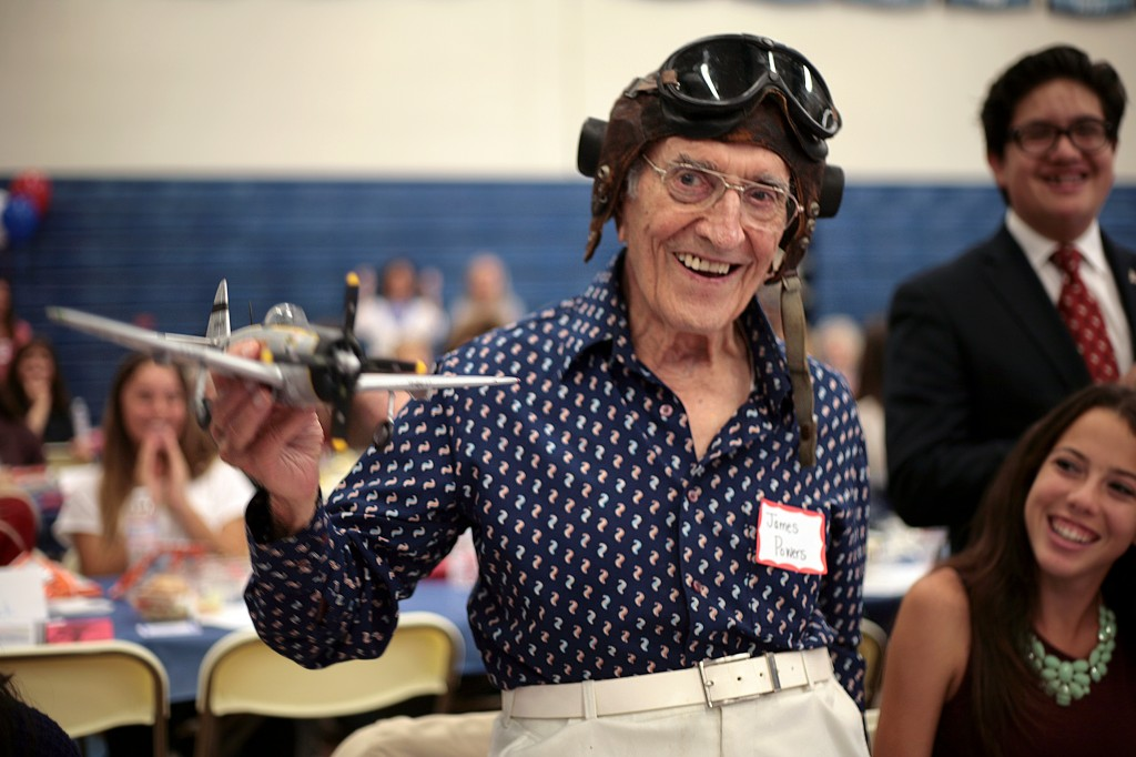 U.S. Air Force WWII veteran James Powers, 93, of Irvine, smiles as his Corona del Mar High School Living History group introduces him on Thursday. The model plane he's holding is similar to those he flew in the war. — All photos by Sara Hall