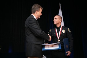 Scott Peotter (left), Field Representative for Assemblyman Allan Mansoor and City Council candidate, shakes the hand of officer Joseph DeJulio, who earned the Lifesaving Award. — Photo by Sara Hall