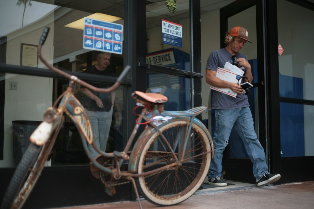 Drew Colome leaves the Bay Station Post Office on Riverside Avenue in Newport Beach on Thursday. The local, who rides his classic bike to the store, didn't know about the lease ending for USPS at the location. — Photo by Sara Hall