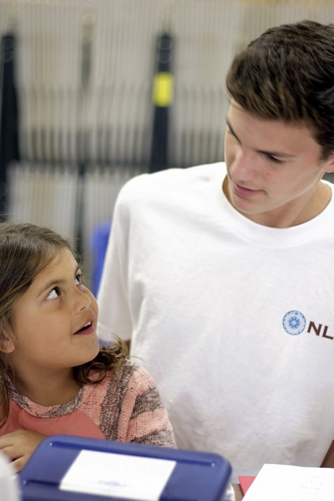 Emilee Menchaca, 6, a first grader in the Project Success program at Adams Elementary School works with National League of Young Men member, Spencer Lawrence, a freshman at Newport Harbor High School, during the league's Meet the Need visit and school supply delivery on Tuesday.