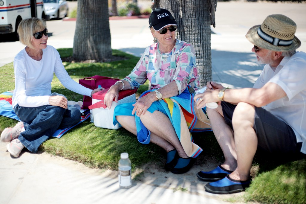(left to right) Pat Kincaid of Mission Viejo, and Diane and David Phillips of Hendersonville, N.C., relax in the shade of a palm tree at Corona del Mar State Beach on Thursday. — All photos by Sara Hall ©