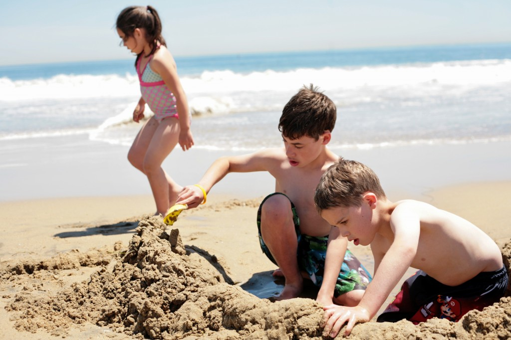 "Gabriel, 11, and Jake, 9, build a ""pool"" in the cool, wet sand as their sister, Becca, 6, plays in the background."