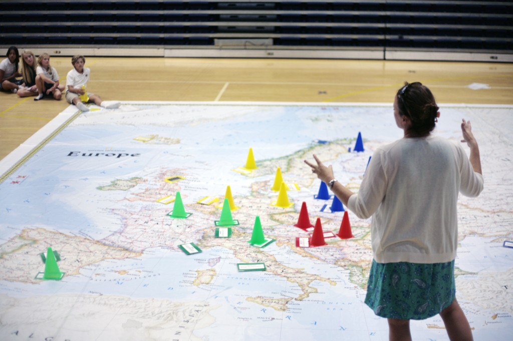 Harbor Day history teacher, Jennifer Fenner, explains an activity that the kids can play - and learn - using the giant National Geographic Traveling Map of Europe on Thursday. — All photos by Sara Hall ©