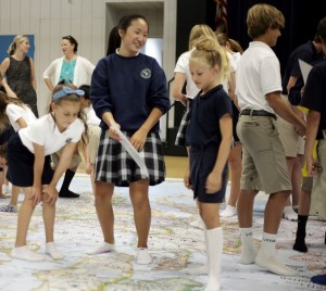 Seventh grader Michaela Phan, 12, helps Ashley Pratt and Isabella Fawaz, both 8, during a geography game on Thursday.