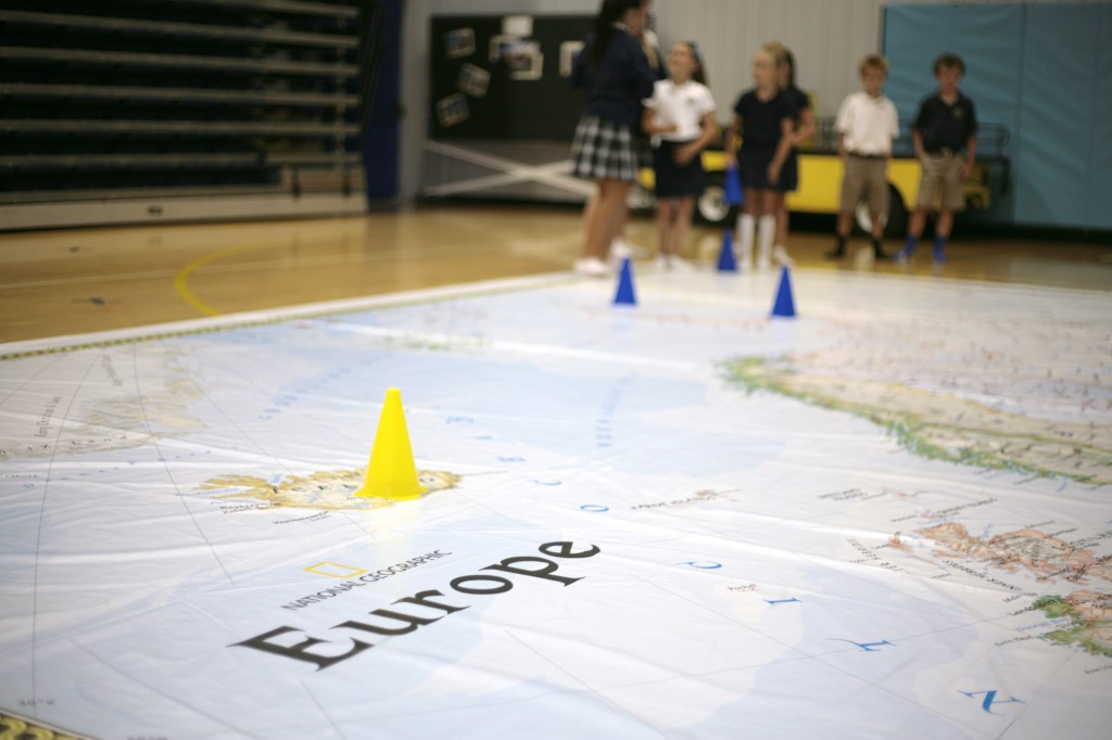 Kids play a game on the giant map of Europe at Harbor Day School on Thursday.