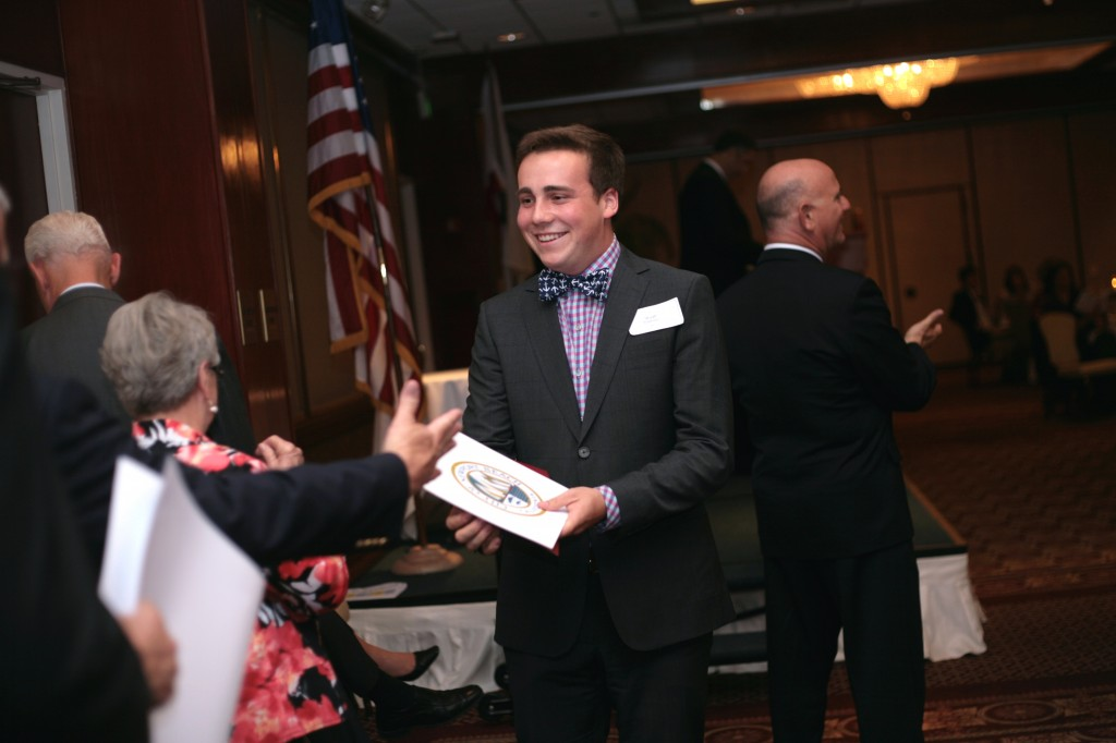 Newport Harbor High School senior Wyatt Robertson gets congratulated by city, school and chamber officials at the Newport Beach Chamber of Commerce Scholarship Awards event on Wednesday. Robertson said his most memorable high school moments were being elected ASB president and playing Willy Wonka in the homecoming rally. He plans on studying physics at Harvard University. — Photo by Sara Hall