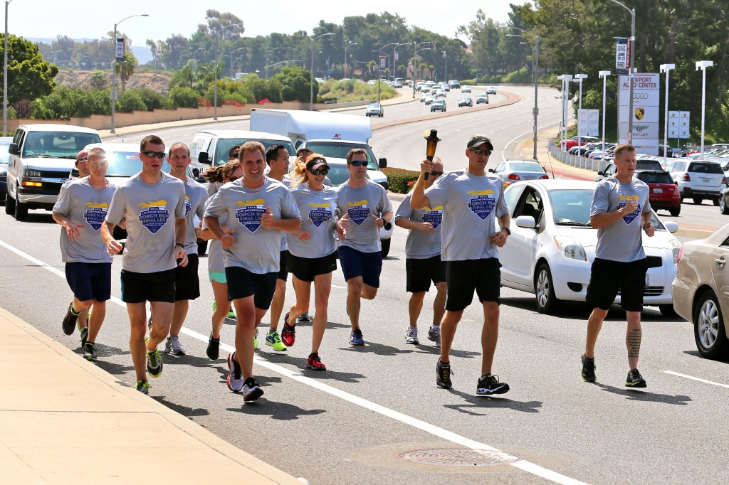 Newport Beach Police Department personnel carry the Flame of Hope as they participate in the Special Olympics Torch Run on Thursday. — Photo by Jim Collins ©