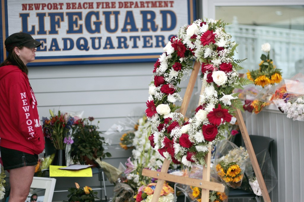 A woman pays her respects Thursday morning as she looks over the flowers, photos, cards, notes and a few flippers that have been placed at the Newport Beach Fire Department's lifeguard headquarters at the Newport Beach Pier as a memorial for Ben Carlson, the NB lifeguard veteran who died Sunday while attempting to rescue a swimmer in distress. — Photo by Sara Hall ©