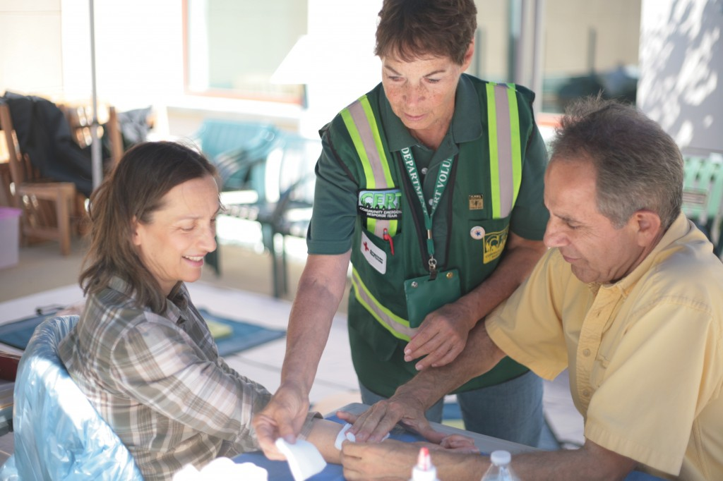 CERT volunteer Marilyn Broughton shows Newport Coast residents Faye and Ali Sadeghi some basic first aid skills during the expo Saturday. — Photo by Sara Hall ©