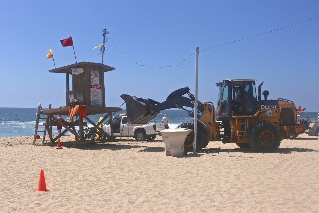 Workers move the lifeguard tower near the Wedge last week after the strong surf washed away sand from the beach.  — Photo by Jim Collins ©