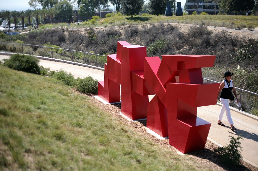 A visitor walks by the large Red Gateway sculpture by Chris Rench at the Civic Center Park on Saturday. — Photo by Sara Hall ©
