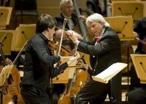 Violinist Joshua Bell performing on stage with Music Director of the Pacific Symphony Carl St.Clair