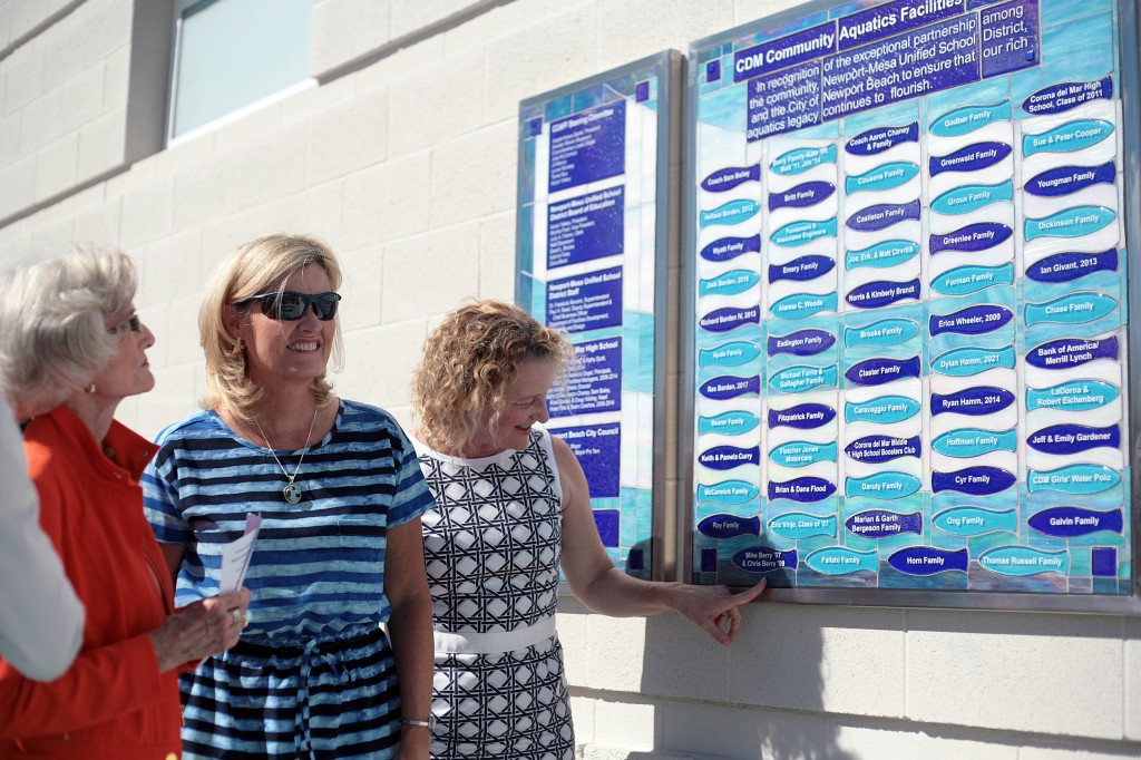 (left to right) former Assemblywoman and California State Senator Marian Bergeson, Newport Beach City Councilwoman Leslie Daigle and Newport Mesa Unified School District board member Katrina Foley examine the commemorative wall at the Corona del Mar High School Marian Bergeson Aquatics Center during the facility's unveiling ceremony on Tuesday. — Photo by Sara Hall ©