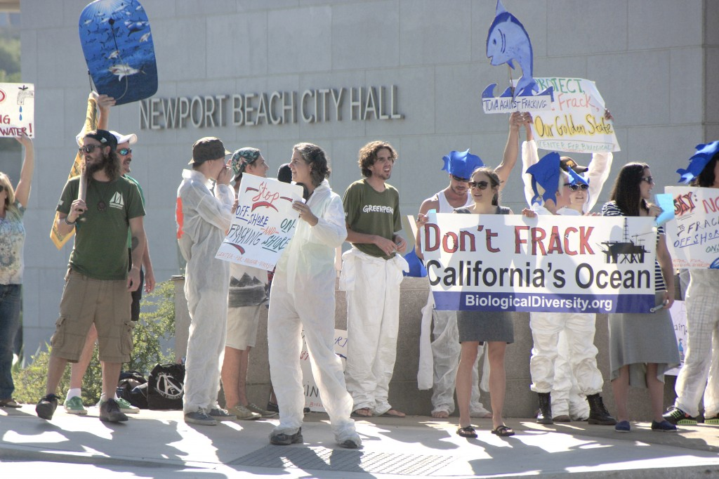 Protesters wave signs and shout chants against fracking Wednesday outside the Newport Beach City Hall, where the CA Coastal Commission was meeting this week. — Photo by Sara Hall ©