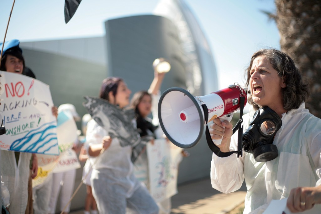 Andrea Weber, a paralegal for the Center for Biological Diversity, leads a group of protesters in a cheer Wednesday outside the Newport Beach City Hall and Civic Center while the California Coastal Commission was meeting inside council chambers. The organization, alongside various other environmental groups, was demonstrating in protest to offshore fracking. Many protesters wore gas masks and hazmat suits. The center delivered a letter urging commissioners to press the federal government for greater oversight of fracking in federal waters off California's coast. — Photo by Sara Hall ©