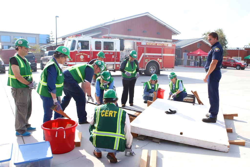 "Fire engineer Alan Baker stands on a wooden wall and watches as CERT volunteers use shoring and cribbing methods to lift it off a ""fire hose victim"" during Drill the Skills on Saturday. Baker jumped up and down on the wall to test the stability of the box cribbing. — Photo by Jim Collins ©"