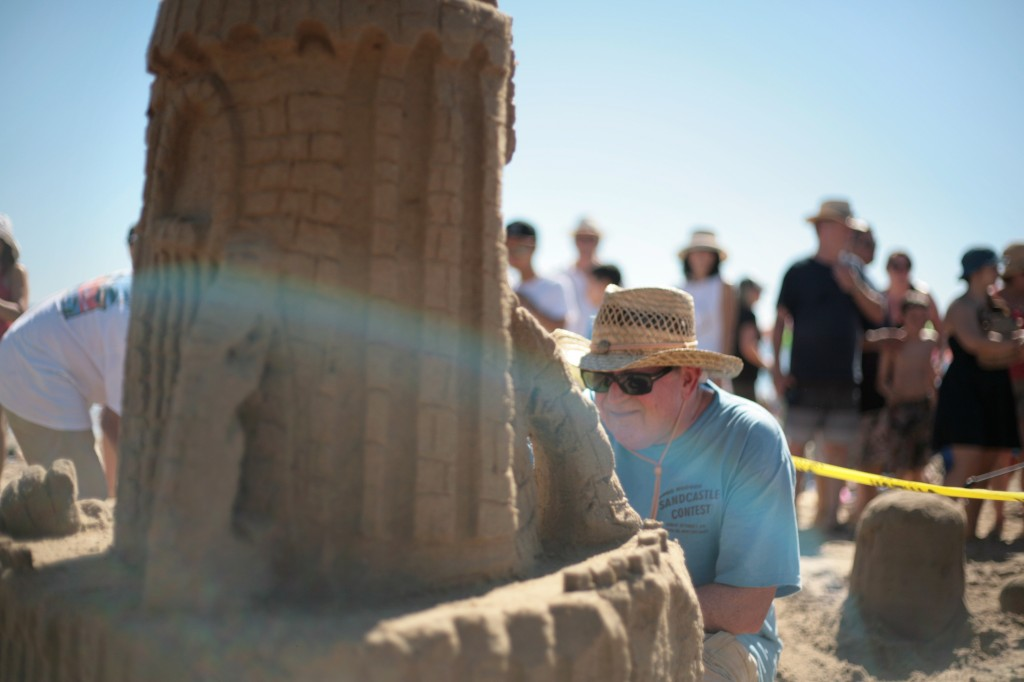 Bob Lank of Mission Viejo works on a sandy structure for his team, the Sand Crabs, during the 53rd Annual Sandcastle Contest on Sunday, presented by the Commodore's Club of the Newport Beach Chamber of Commerce. The Sand Crabs (and their secondary entry, Sand Crabs Too) ended up winning the People's Choice Award for Best Creation and second place for Most Unique Sandcastle. — Photo by Sara Hall ©