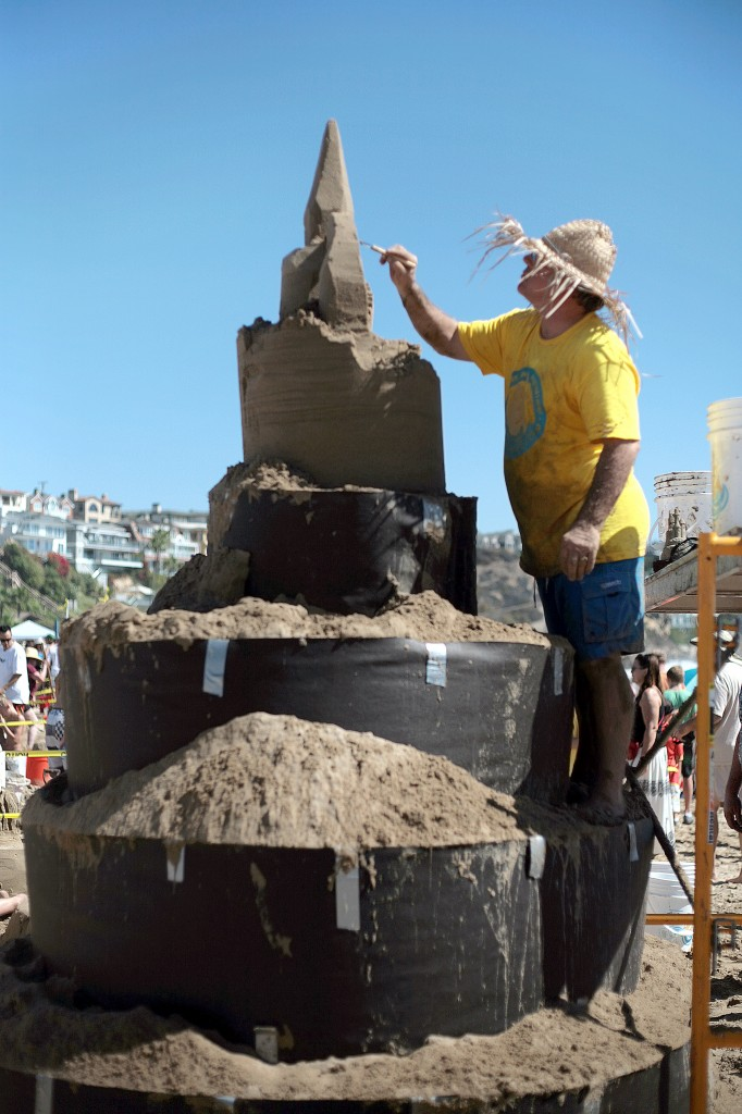Chris Crosson, co-owner and president of Doggy Walk Bags, Inc., and Sandcastle Kits, works on a large castle structure for his company's team during the 53rd Annual Sandcastle Contest on Sunday, presented by the Commodore's Club of the Newport Beach Chamber of Commerce. His team finished in first place for Most Unique Sandcastle. — Photo by Sara Hall ©