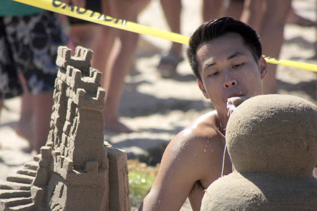 Andy Nguyen of team San Diego Sandcastle Silicate Based Life Forms blows loose sand from his sculpture. The team took home top honors, the Commodores Award of Overall Best Creation. — Photo by Sara Hall ©
