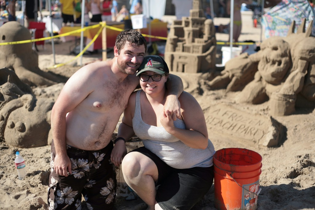 """Eric Walker of Irvine and Stephanie Croft of Mission Viejo in front of their group's """"Frozen"""" design. They were on Team ASCE OC, the American Society of Civil Engineers of Orange County, and ended up winning third place for Most Unique Sandcastle. — Photo by Sara Hall ©"""