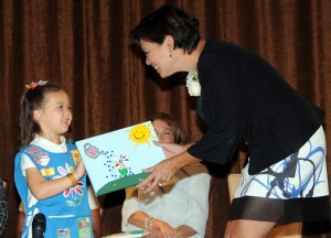 """Girl Scout Daisy Kassidy Lee presents an art piece she created for honoree Betty Mower Potalivo, illustrating how Betty """"makes people's money grow."""""""