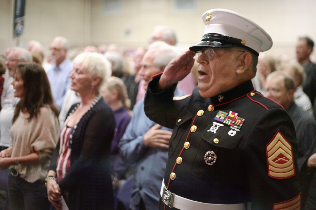 Veteran Jesus Rivera of Irvine salutes as he sings the national anthem during the event. The Texan native served in the U.S. Marines from 1970 to 2000.  — Photo by Sara Hall