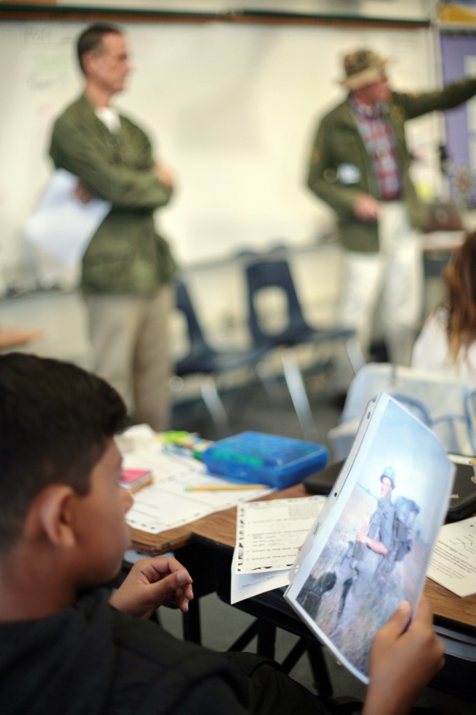 A student  looks over a photo from Vietnam as (left) Mike Flenniken and Mike Dowd talk to the class.  — Photo by Sara Hall ©