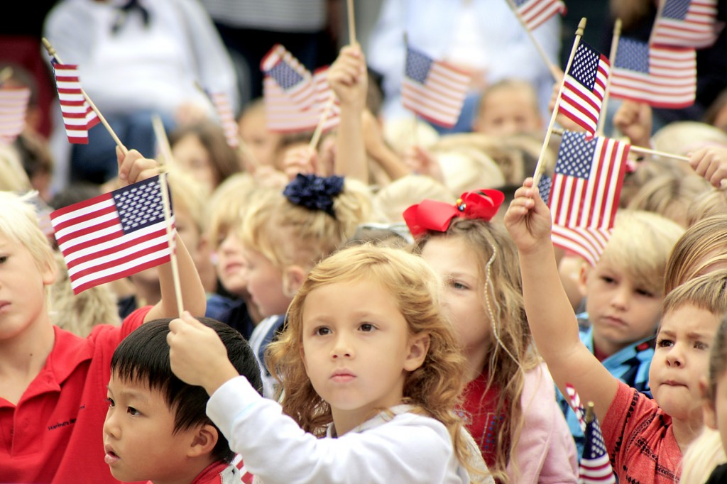 Students at Mariners Elementary School wave flags during a patriotic song on Veterans Day. — Photo by Sara Hall