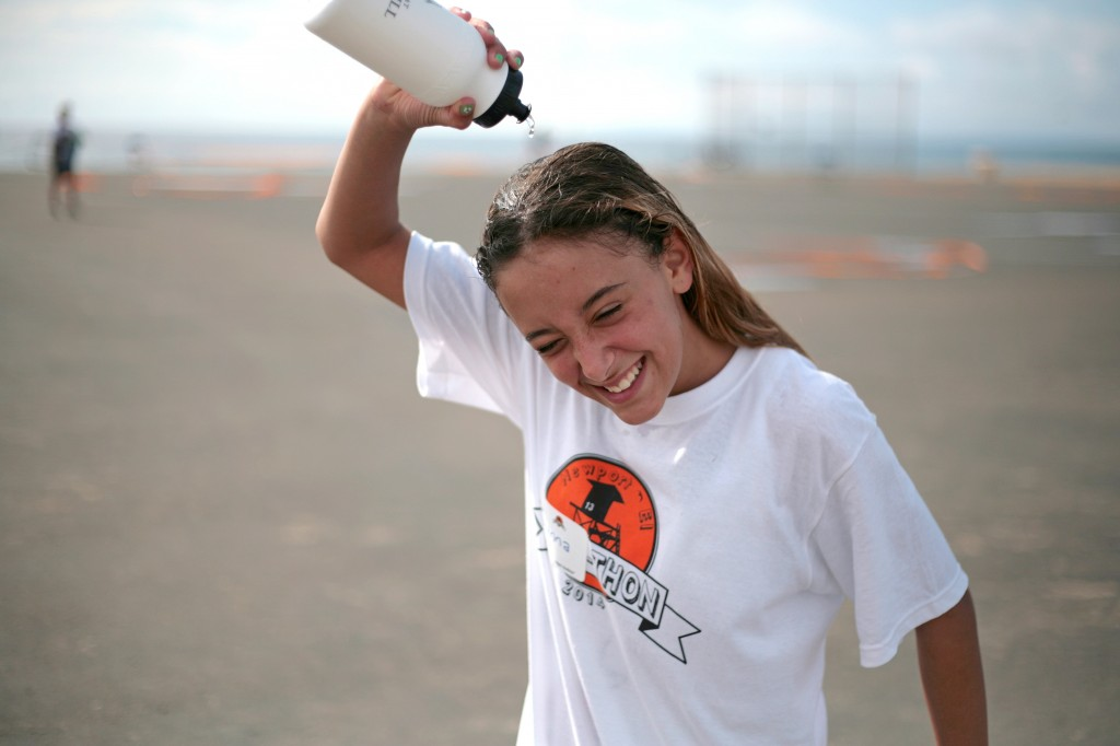 Gianna Milks, 12, a sixth grader at Newport El, cools down by dousing herself in water after running laps at the annual fundraising Jog-A-Thon. — Photo by Sara Hall