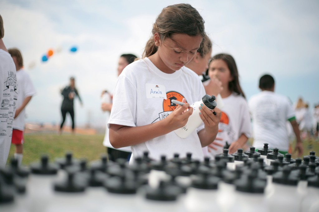 Anela Brown, 10, a Newport El fifth grader, writes her name on a water bottle during the Jog-A-Thon. — Photo by Sara Hall