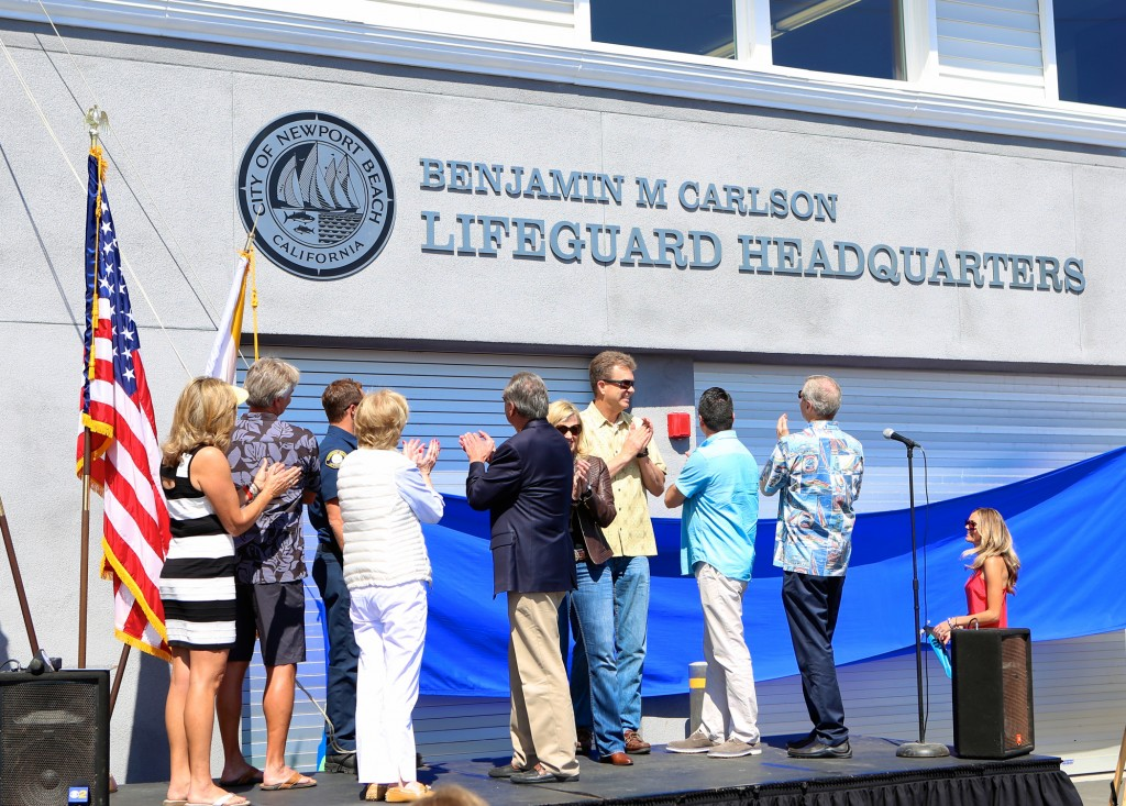 Newport Beach City Council members and other VIPs applaud the unveiling of the Benjamin M Carlson Lifeguard Headquarters. — NB Indy Photo ©