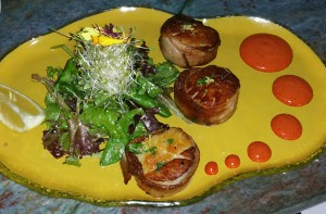 Pan seared diver scallops wrapped in triple smoked apple wood bacon served with achiote aioli, at Fly 'N' Fish
